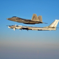 F 22 Escorting Tu 95 Wallpaper